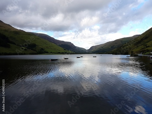 The sky reflects in the water of this vast lake and mountain landscape in Wales. - 249853355