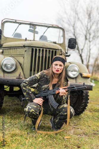 Woman in military uniform with rifle and car © alfexe