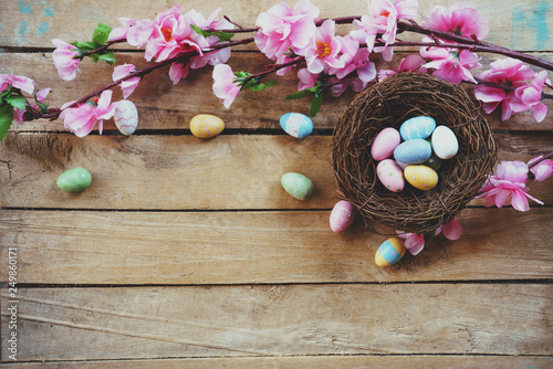 Leinwandbild Motiv Cherry blossom Artificial flowers and easter egg in nest on vintage wooden background with copy space.