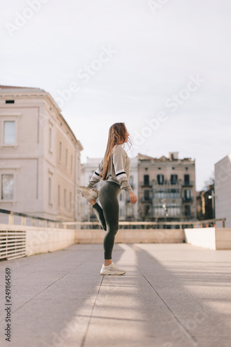 obraz lub plakat young woman doing workout in the city