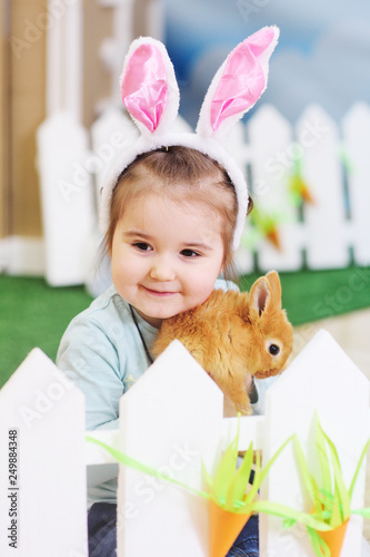 Leinwandbild Motiv baby girl with Bunny ears holding a small red fluffy rabbit. Easter concept