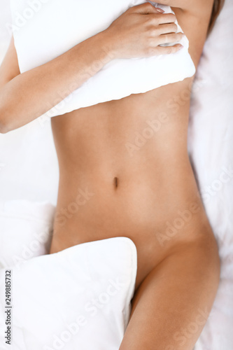 Leinwanddruck Bild Adult naked woman lying in bed in the morning