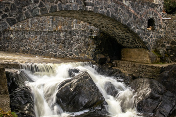 Small stone bridge on river in sunrise. Fast river and waterfall under the bridge.