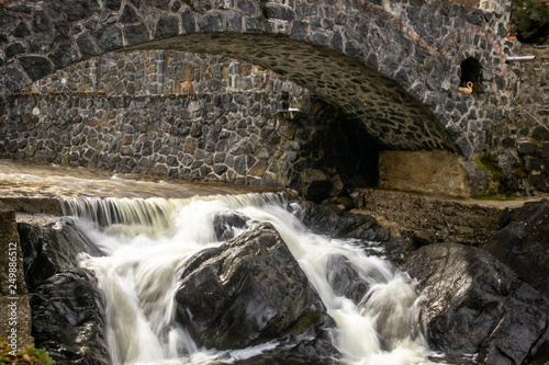 Small stone bridge on river in sunrise. Fast river and waterfall under the bridge. - 249886512