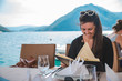 young pretty woman sitting in restaurant at seaside with mountains on background