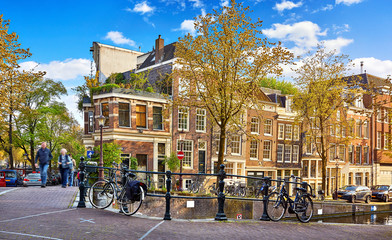 Street of Amsterdam city. Netherlands. Bridge over channel with traditional dutch houses and bicycles. Evening time warm sunlight, blue sky with clouds. Spring cityscape, green and yellow autumn. © Yasonya