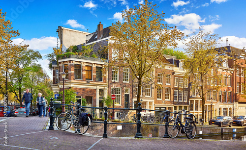 Street of Amsterdam city. Netherlands. Bridge over channel with traditional dutch houses and bicycles. Evening time warm sunlight, blue sky with clouds. Spring cityscape, green and yellow autumn. - 249888792