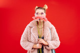 Fashionable blonde woman holding three beautiful flowers