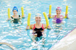 Leinwanddruck Bild - Group of active senior women exercising in swimming pool, holding pool noodles and smiling at camera, copy space