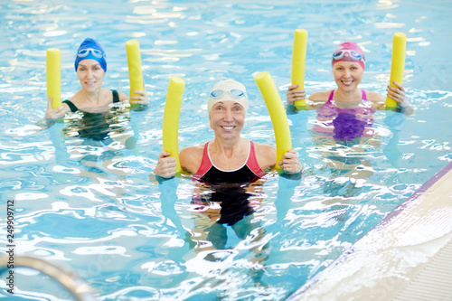 Leinwanddruck Bild Group of active senior women exercising in swimming pool, holding pool noodles and smiling at camera, copy space