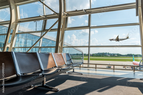 Leinwanddruck Bild Passenger seat in Departure lounge and landing plane, view from airport terminal. Vacation, transport and travel concept