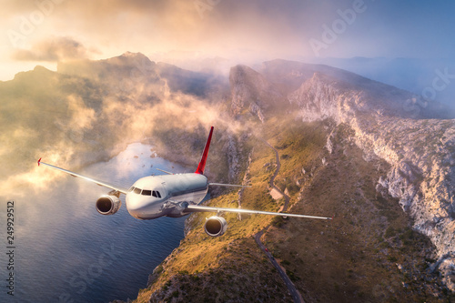 Leinwanddruck Bild Airplane is flying over mountains and low clouds at sunset in summer. Landscape with passenger airplane, sky in clouds, rocks, sea, sunlight. Business travel. Commercial plane. Aerial view of aircraft