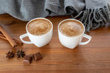 Two cups of coffee with cinnamon sticks, anise and chocolate near warm scarf on wooden table.