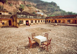 Outdoor restaurant with one table under walls of historical fort in Rajasthan. Rural cafe at breakfast time, India
