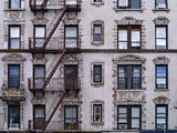 old New York apartment building with external fire escapes, window air conditioners, and ornate trim around windows - 249939515
