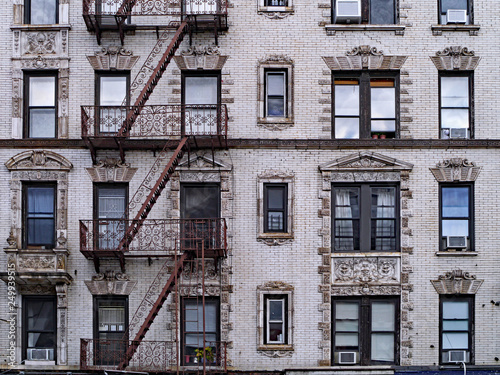 old New York apartment building with external fire escapes, window air conditioners, and ornate trim around windows