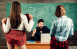 Leinwanddruck Bild - Bearded sexology teacher looks at two sexy female students. Erotic education and sex Symbols on chalkboard. Anatomy lesson and sex education in high school.