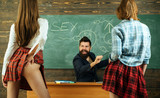 Symbols on chalkboard. Lesson and sex education in high school. Sexology teacher looks at two sexy female students. Erotic education.