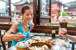 Chinese woman eating at Shanghai restaurant Xiao long bao / xiaolongbao soup dumplings typical food China travel vacation. Asia tourist girl eating Shanghainese steamed dumpling buns with chopsticks.