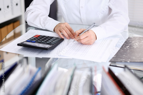 Unknown bookkeeper woman or financial inspector making report, calculating or checking balance, close-up. Business portrait. Audit or tax concepts © rogerphoto
