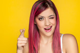 Young smiling woman with pink hair on yellow background - 249996580