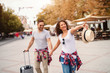 Smiling cute mature couple holding hands and walking on the street on springtime. Woman pointing with finger while man carrying luggage.