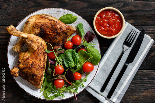 Grilled chicken leg quorters with salad mix and tomatoes. - 250003930