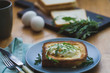 sandwich with egg and arugula on a plate is on the table - 250012519
