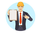 Businessman in construction helmet pointing at a clipboard - 250015365