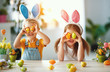 Leinwanddruck Bild - Happy easter! funny funny children   with ears hare getting ready for  holiday.