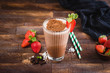 Leinwandbild Motiv Chocolate milkshake or cocktail in glass cup on brown wooden background. Protein milkshake with strawberry