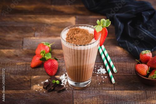 Leinwanddruck Bild Chocolate milkshake or cocktail in glass cup on brown wooden background. Protein milkshake with strawberry