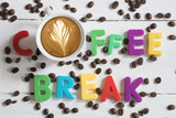 Coffee beans scattered on white table with coffee break message