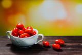 cherry tomatoes on wooden board with blurred background