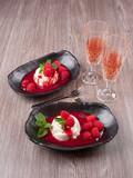 Vanilla bean pannacotta with raspberry coulis, fresh raspberries, and mint leaves