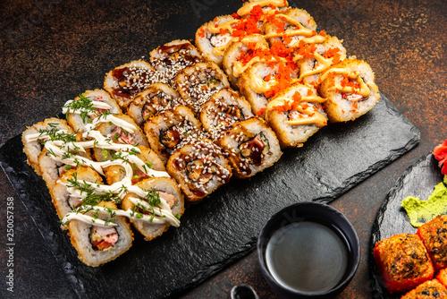 Big sushi set with variety of sushi rolls,on stylish dark background.