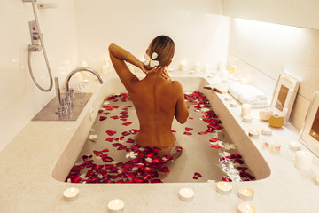 Woman relaxing in spa bath with flower petals © Alena Ozerova