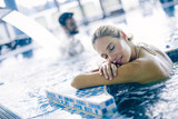 Portret relaksuje w pływackim basenie piękna kobieta