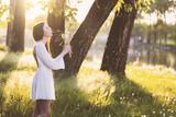 Woman wearing a white dress blowing a dandelion