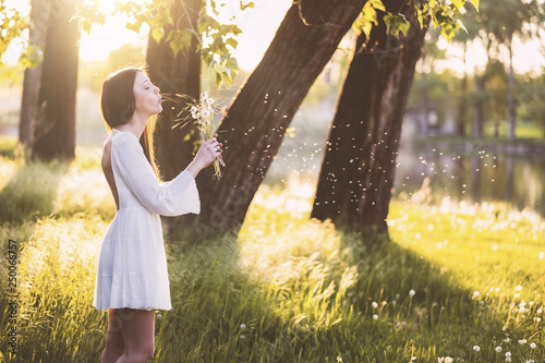 Woman wearing a white dress blowing a dandelion