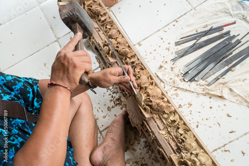 Hands of a carpenter making traditional wood  carving in Bali - 250067189