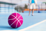 Boy practicing basketball sport on blue court and ball