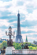 Beautiful view of Eiffel Tower against the white clouds on the blue sky on sunny summer day. Vertical picture