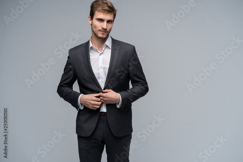 Leinwanddruck Bild Portrait of serious handsome man in gray suit buttoning jacket against gray background
