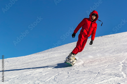 mata magnetyczna snowboarder quickly rolls down the mountain in loose snow against a blue sky on a sunny day. Copy space