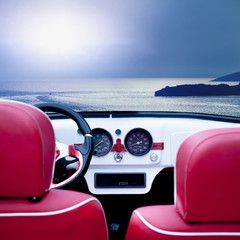 Summer time and red retro car on beach. Interior of classic vintage car against sea background. Travelling, rest, holiday concept.