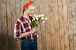 Leinwandbild Motiv cheerful woman smiling while looking at tulips