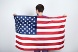 Beautiful young man holding an American flag on grey background - 250098756