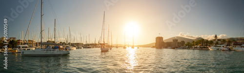 Sailing yachts in harbour during sunset.