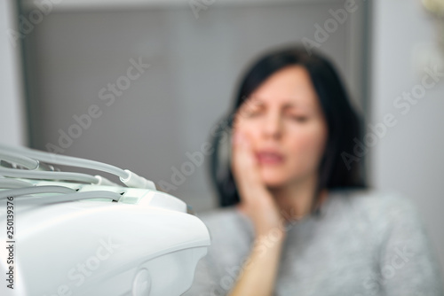 Medicine, dentistry and healthcare concept. Woman with tootache at dental clinic, focus on the foreground, on medical equipment. - 250139376